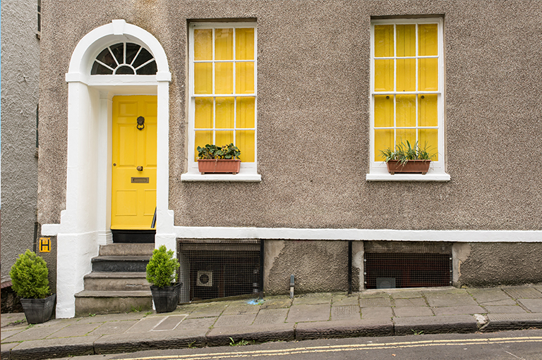 Yellow door house exterior photo with yellow windows and plants on street,