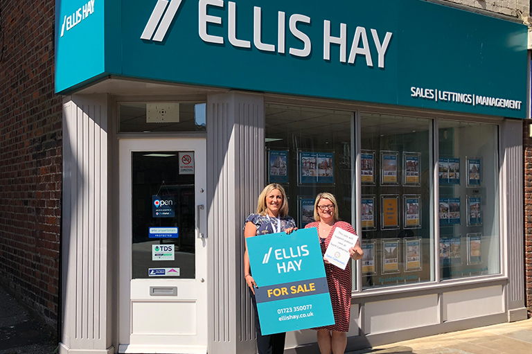 Representative of Saint Catherines and Partner, Samantha Hay in front of Ellis Hay office holding Sales board and Saint Catherine's document.